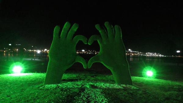 Зеленые руки, сложенные в сердечко ночью - Новороссийск район Мыса любви